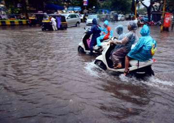 Vehicles wade through a flooded road after heavy...