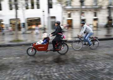 Pice - A woman and a man ride their bicycles on...