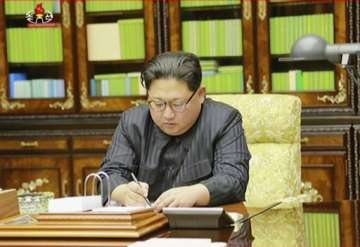 North Korea's leader Kim Jong Un signing what is...
