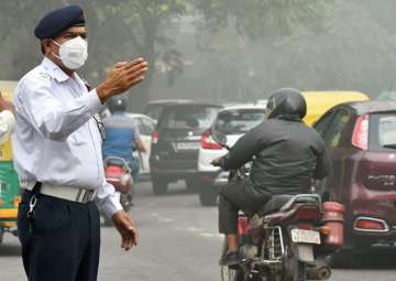 Traffic policemen wear masks to protect...