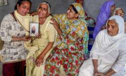 Family members grieve by a portrait of one of the 39 Indian
