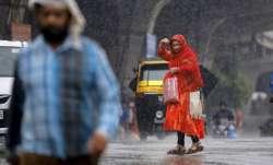 Thunderstorm Alert Latest News: A woman crosses a road amid