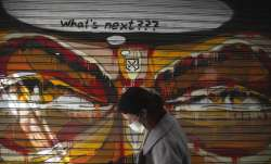 A woman wearing a face mask to protect against coronavirus, passes in front of graffiti painted on t