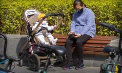 A woman and an infant wear face masks as they sit in the sun in Beijing, Wednesday, April 1, 2020. C