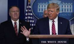 In this March 20, 2020, file photo, with Secretary of State Mike Pompeo to the rear, U.S. President