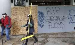 A woman helping to clean up downtown walks near graffiti Sunday, May 31, 2020, in Seattle, following