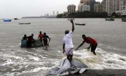 Fishermen pull their nets out of the Arabian Sea in Mumbai, India, Wednesday, June 3, 2020. A storm