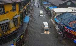 Mumbai: Vehicles ply on a waterlogged street during heavy
