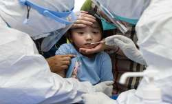 FILE | A child reacts to a throat swab during mass testing