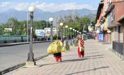 Workers walk on a pavement during lockdown imposed in Jammu