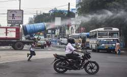 Municipal corporation workers use a mist cannon to sanitize