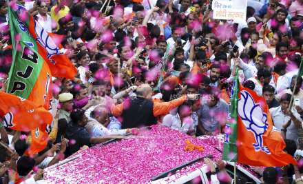 BJP President Amit Shah is showered with flower petals as